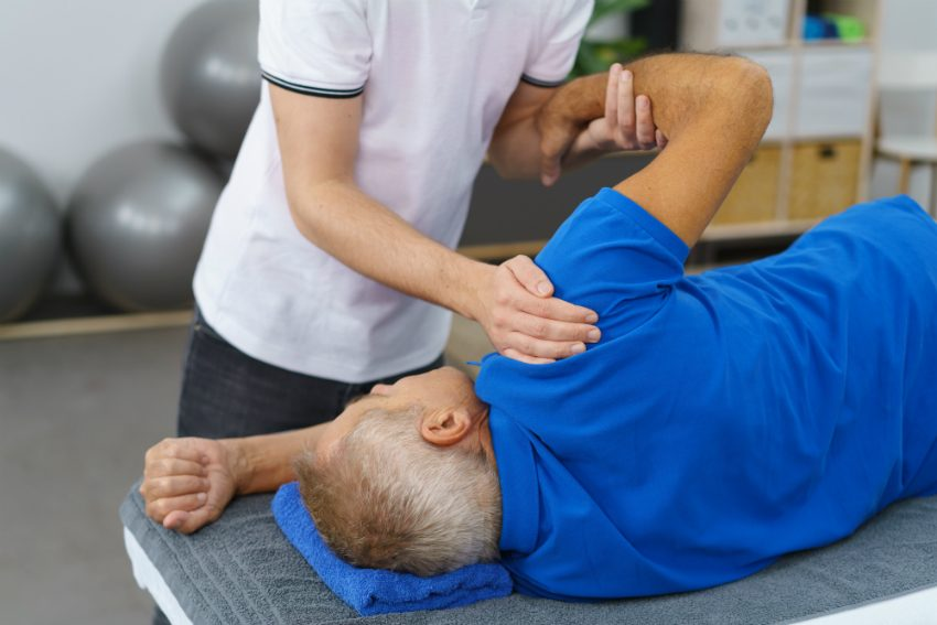 Physiotherapist doing shoulder exercises with patient